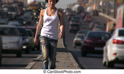 girl walks on highway middle in city