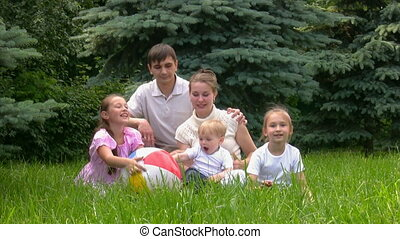 family with ball sits in summer park - happy family of five...