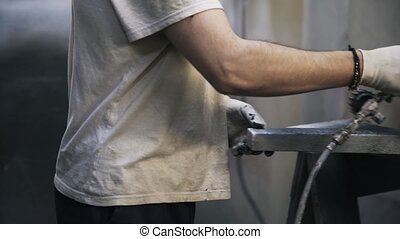 Carpenter is painting a corner of a frame using a black...