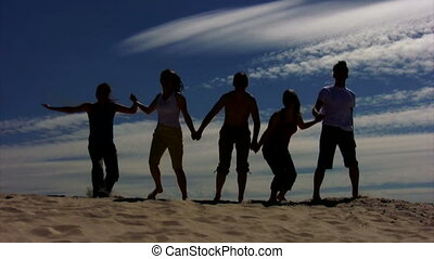 five persons having joined hands jumps on sand, sky in...