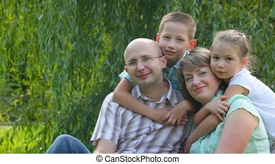 family sits on grass in park