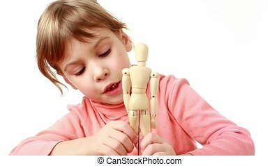 girl raises arms and legs of human wooden figure and moves...