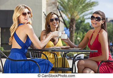 Three Beautiful Young Women Having Coffee At City Cafe