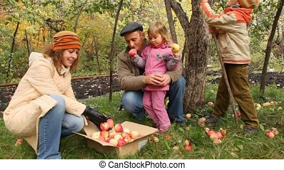 family from grandfather, mother, son and daughter collects apples