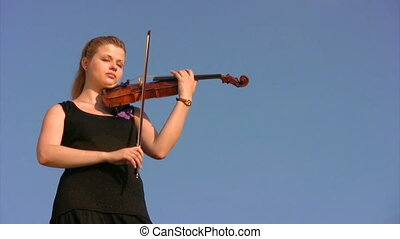 young woman plays violin against blue sky - young woman in...