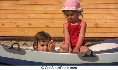 little girls sits in inflatable water pool - two little...