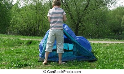 The boy establishes tent on a glade in summer day. Time...