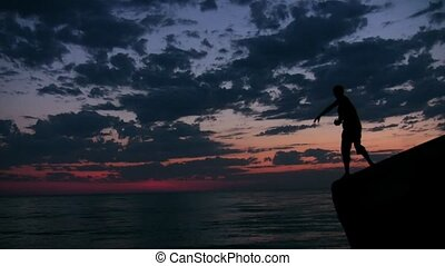 man stands on rock and throws pebbles into sea under sunset...