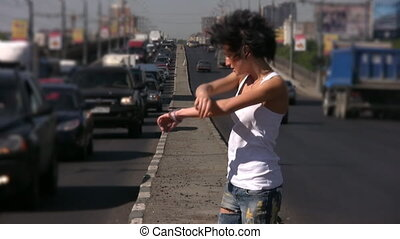 girl dancing on highway middle in city, blurred moving cars