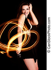 Woman light painting - A young woman dancing with vibrant...