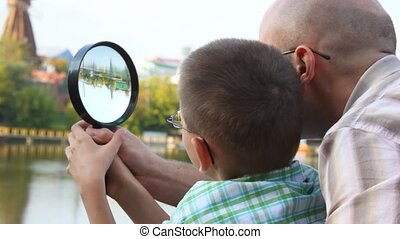 father and son standing on bank of river and looks through...