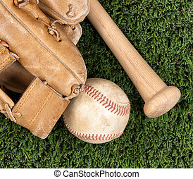 Close up overhead view of old baseball equipment on grass -...