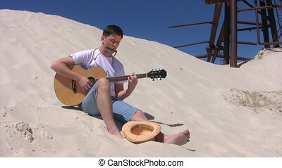 man sits on beach and plays guitar - happy man sits on sandy...
