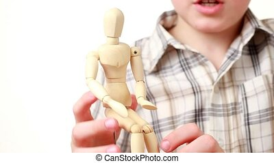 boy makes wooden figure of human scratchs its head
