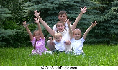 family raised hands sits in park - happy family of five with...
