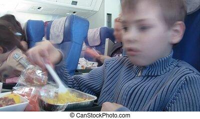 serious boy eats in plane salon
