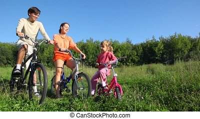 family on bicycles talks in park - happy family of three...