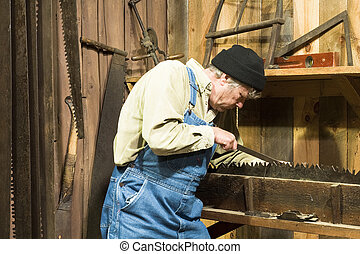 man sharpening an old saw - man sharpening an old loggers...