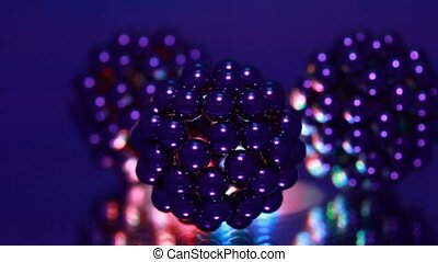 Three figures consisting of metallic balls rotate around its...