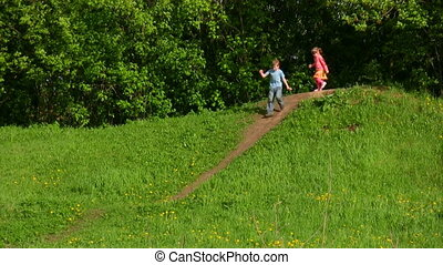 boy and girl running down from hill - boy and little girl...