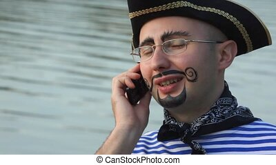 man in pirate costume is speaking on the phone, boat with...