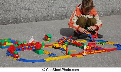 boy collects structure of toy railway in street