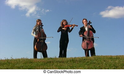 three musicians plays violoncellos and violin stands on hill...