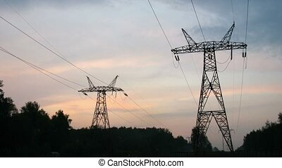 The sky darkens over transmission equipment and forest