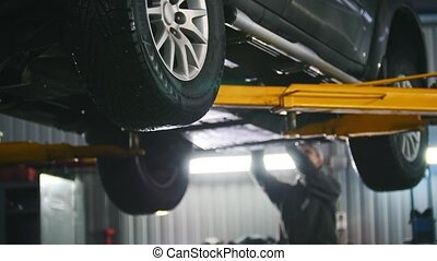 Car lifted in automobile service for repairing, worker...