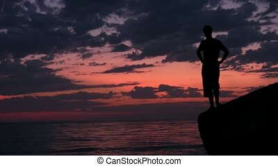 silhouette of young man stands on rock against sunset
