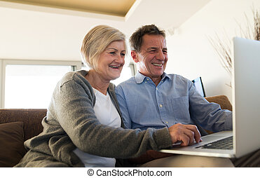 Senior couple with laptop sitting on a couch in living room...