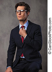young seated business man fixing his tie