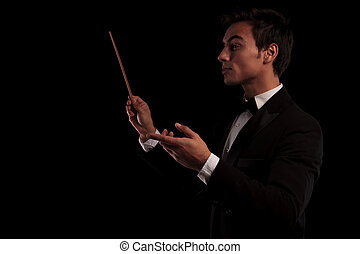 side view of an elegant music conductor holding a batton