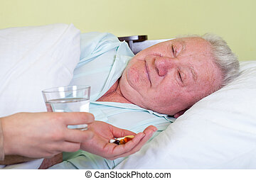Sick old man in bed, receiving his pills - Picture of a sick...