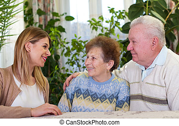 Elderly couple with happy caretaker - Picture of an elderly...