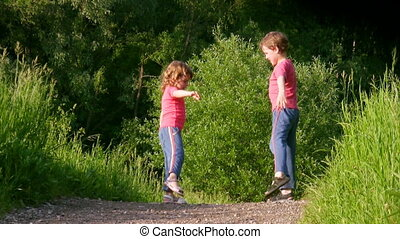 girl and boy exercising in summer forest