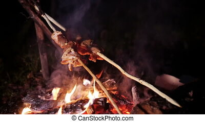 Roast meat on a stick over a campfire roasting directly.