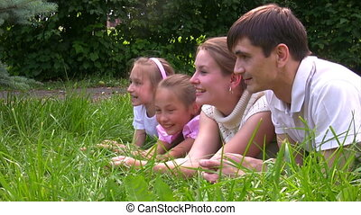 family lying on grass in summer park