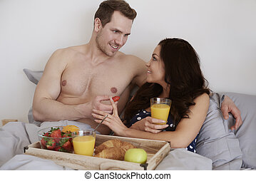 Man feeding his beloved with strawberry fruit