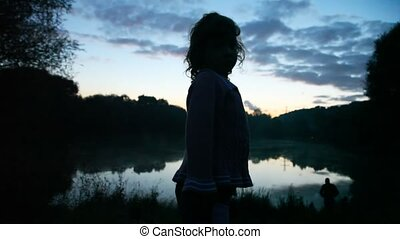 girl standing at lake in wood