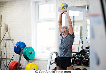 Senior man in gym working out using kettlebells.
