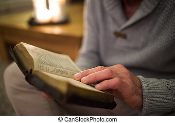 Unrecognizable man at home reading Bible, burning candles...