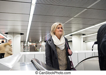 Senior woman standing at the escalator in Vienna subway