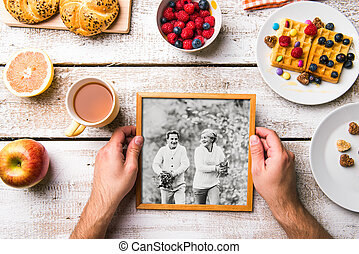 Hands holding picture of seniors, breakfest meal. Studio...