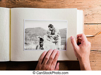Hands holding photo album with picture of senior couple....
