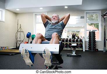 Fit senior man in gym working his abs, doing crunches. - Fit...