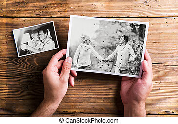 Hands holding pictures of senior couple. Studio shot, woo -...
