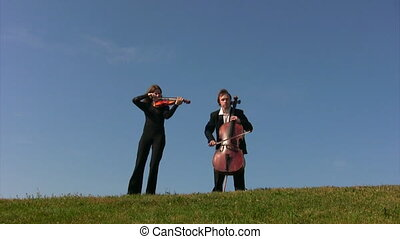 man plays violoncello, woman plays violin on meadow against...