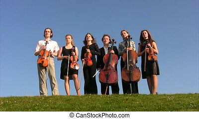 six musicians with stringed instruments stands on hill...