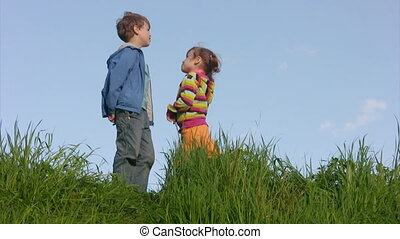 boy and little girl talking in meadow against sky, then...